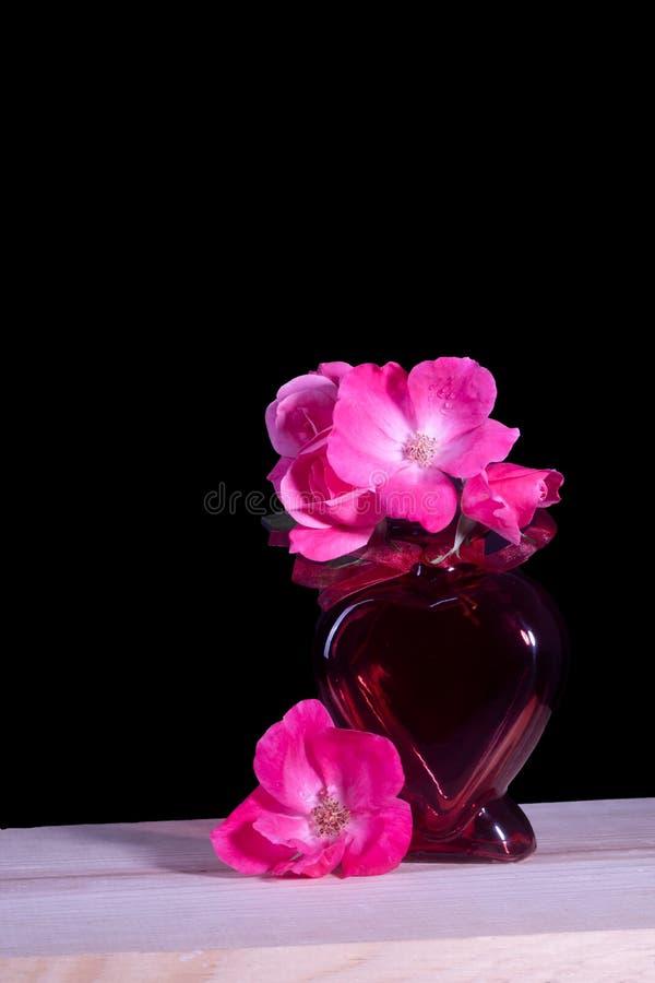 Un vaso rosso del cuore ha riempito un mazzo di belle rose rosa fotografia stock libera da diritti