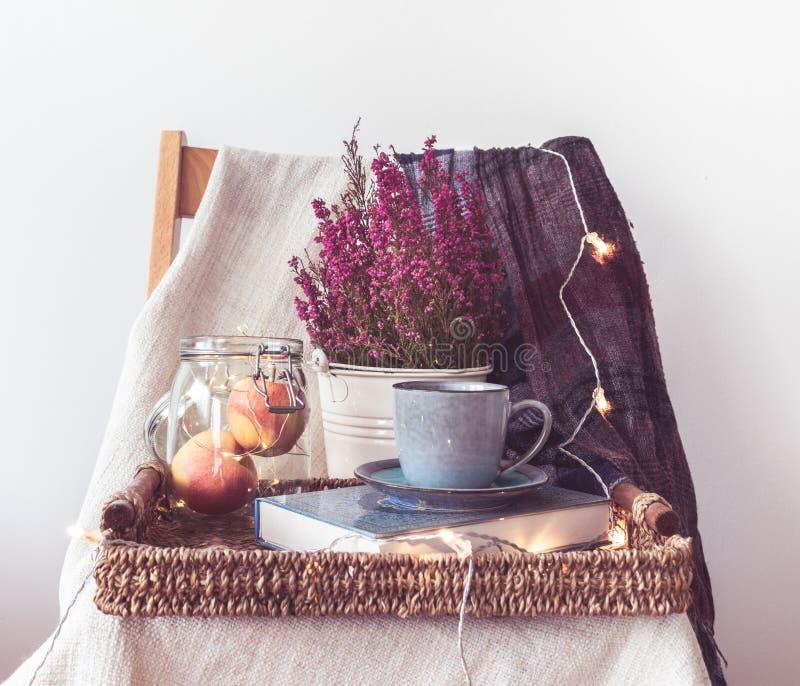 Un vassoio con una tazza di caffè, mele in un barattolo, catena leggera, fiori e una sciarpa fotografia stock