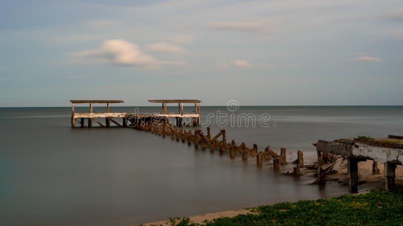 Un vecchio bacino di pesca dilapidato crolla in mare a Pak Nam Pran Thailandia immagine stock