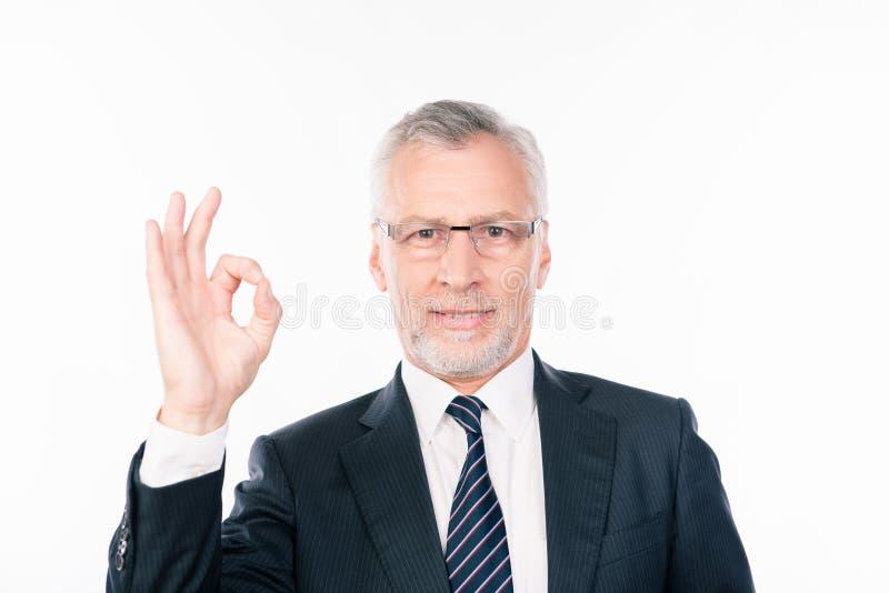 Un vecchio e intelligente uomo d'affari che mostra il gesto ok fotografie stock libere da diritti