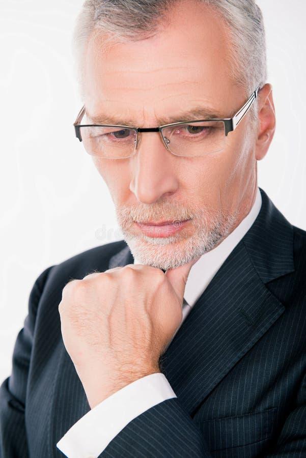 Un vecchio e intelligente uomo d'affari con gli occhiali per prendere una decisione immagini stock libere da diritti