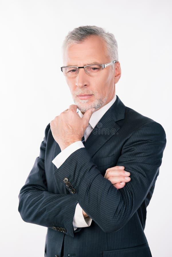 Un vecchio e intelligente uomo d'affari con occhiali che si mette la mano sul mento immagine stock
