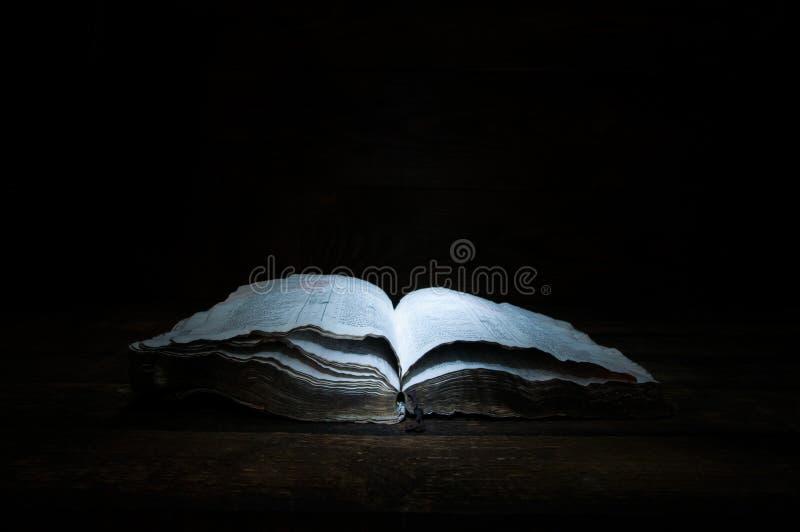 Un vecchio libro aperto sta trovandosi su una tavola di legno nello scuro Una luce splende sul libro da sopra Bibbia santa immagine stock libera da diritti