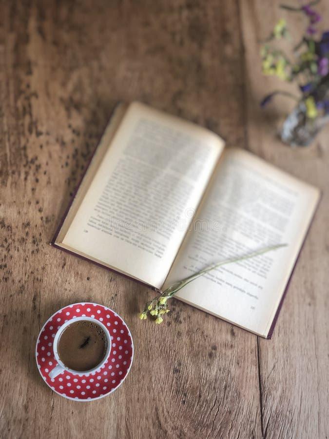 Un vecchio libro e una tazza di caffè sulla tavola di legno fotografia stock