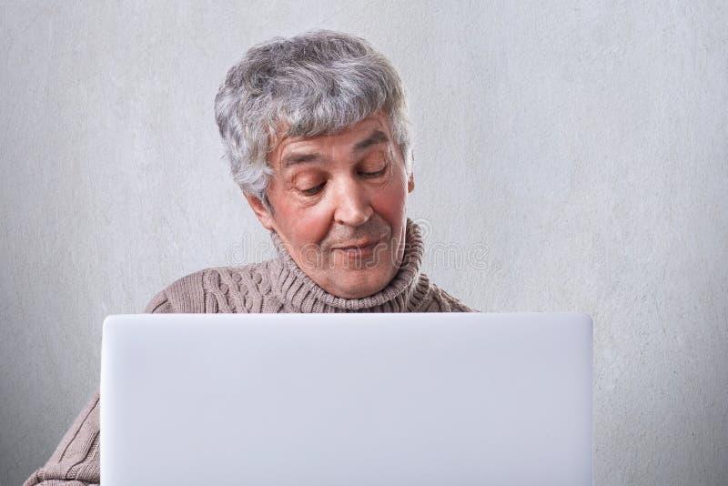 Un vecchio maschio soddisfatto avendo conversazione online sul suo computer portatile mentre collocando a casa Un usi maturo attr fotografie stock libere da diritti