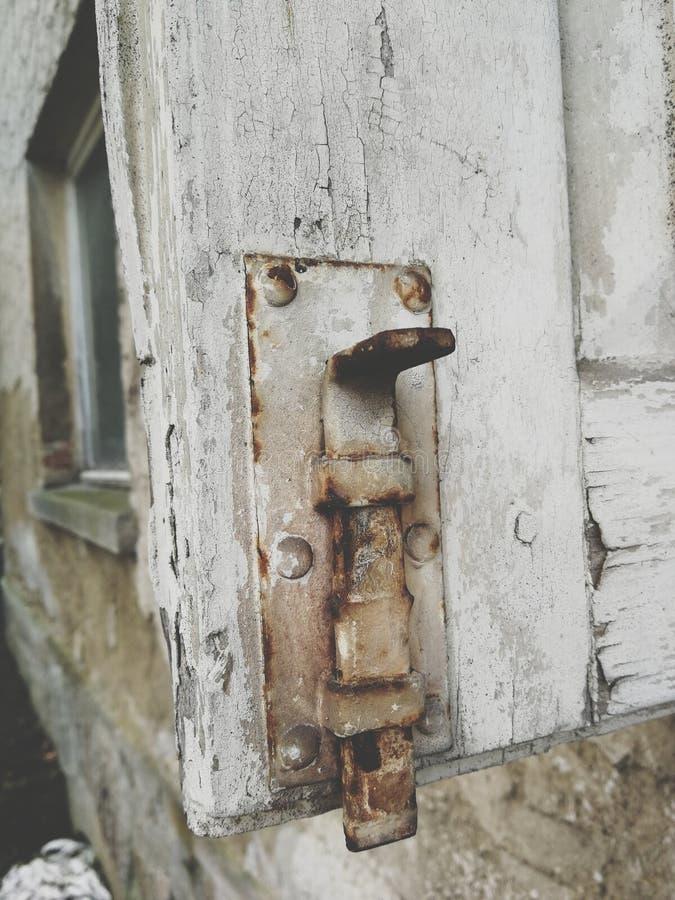Un vecchio palo di legno arrugginito con la serratura immagini stock libere da diritti