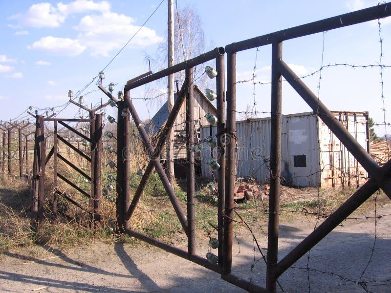 Un vecchio recinto di ferro con un cancello arrugginito chiuso vieta di recarsi nel territorio di una stazione tecnica abbandonat immagine stock libera da diritti