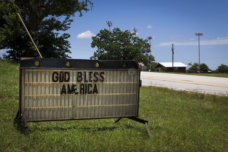 Un vecchio segno arrugginito con il ` Dio di parole benedice il ` dell'America dal lato di una strada campestre nel Texas rurale fotografia stock libera da diritti
