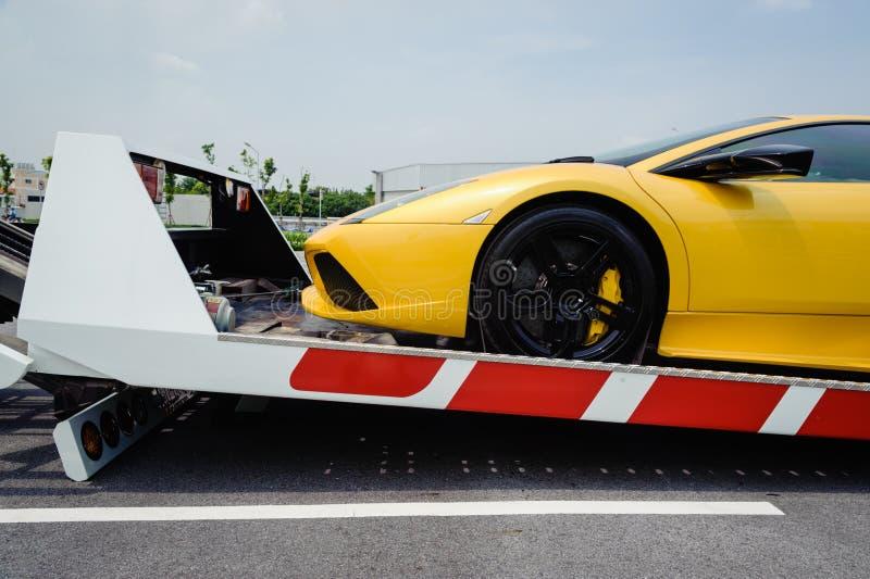 Un vehículo quebrado atado con correa abajo a la plataforma de la grúa de la cama plana foto de archivo libre de regalías