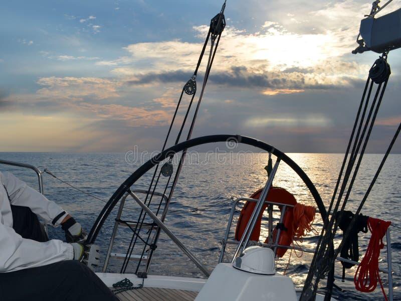 Un veleggiatore che esegue un yacht di navigazione che lascia una tempesta nel mare aperto immagine stock