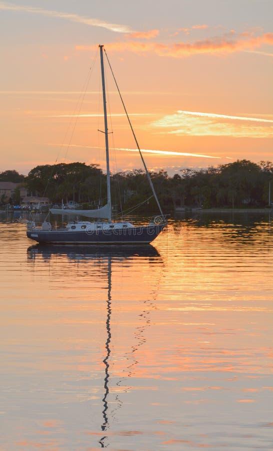 Un velero en la puesta del sol foto de archivo