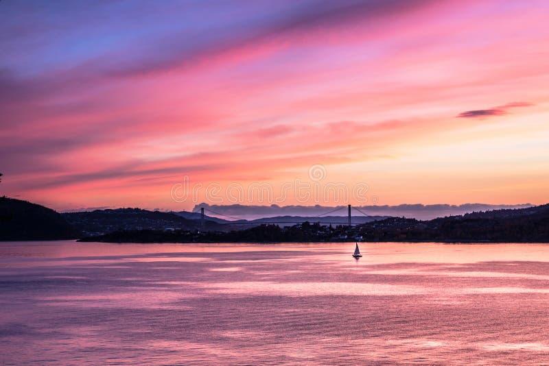 Un velero solitario en la puesta del sol rosada fotografía de archivo libre de regalías