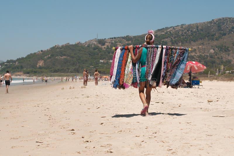 Un vendedor ambulante de la mujer con mantones en una playa española en Tarifa imágenes de archivo libres de regalías