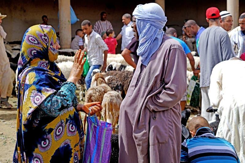 Un vendedor del expedidor contrató con una mujer del Berber en el souk de la ciudad de Rissani en Marruecos imagen de archivo libre de regalías