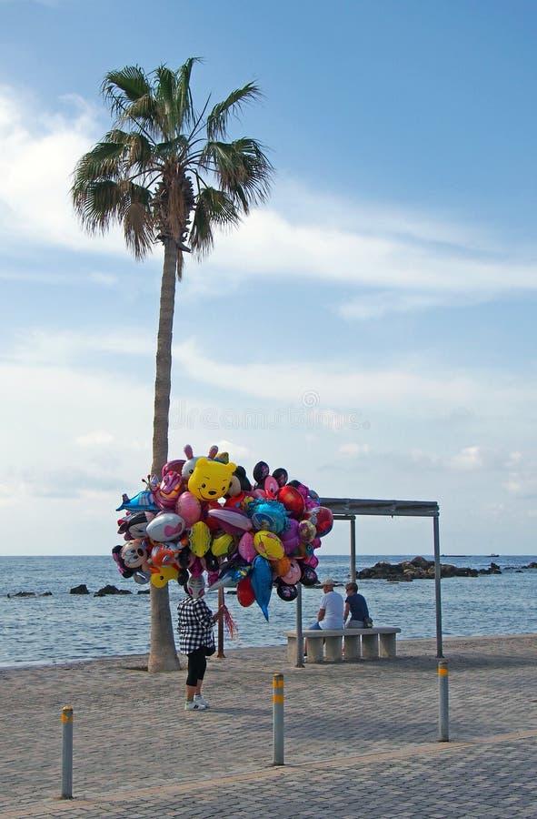 un vendedor del globo camina más allá de dos turistas sentados en la playa en Paphos Chipre imagen de archivo