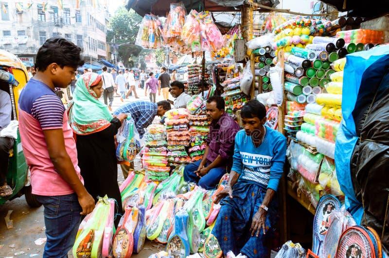 Un vendedor está vendiendo artículos plásticos en el mercado callejero imagen de archivo libre de regalías
