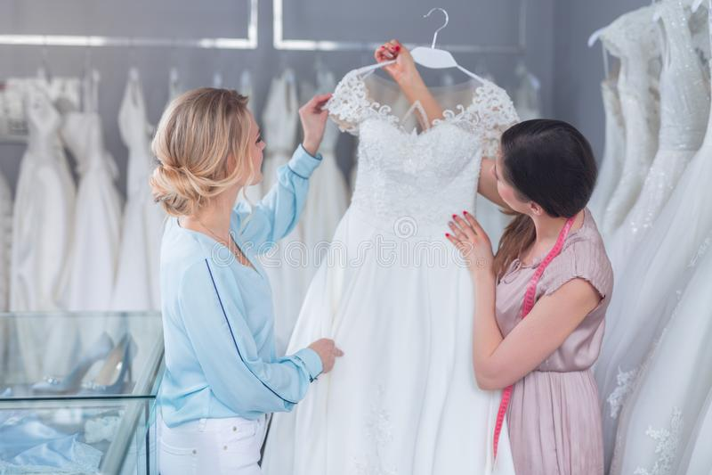 Un vendedor y un cliente jovenes con un vestido de boda imagen de archivo libre de regalías