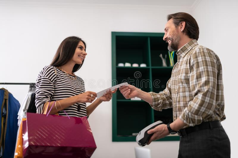 Un vendeur doué responsable fournissant à une femme des sacs photos libres de droits