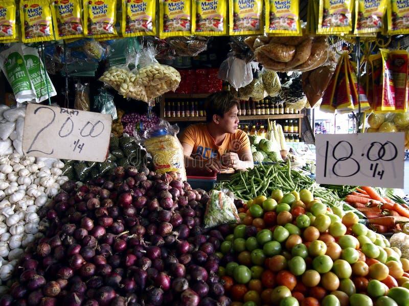 Un vendeur du marché à l'intérieur d'une stalle de fruits et légumes sur un marché public photographie stock