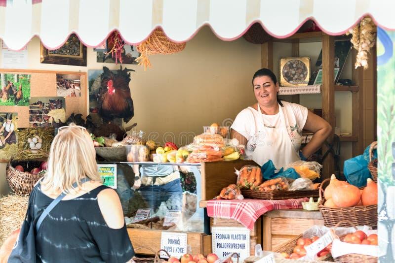 Un vendeur féminin parlant avec bonheur avec un client à son épicerie sur un marché public dans la fente, Croatie photographie stock libre de droits
