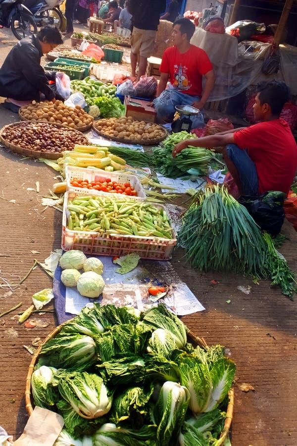 Un venditore ambulante del gruppo in un mercato bagnato immagine stock