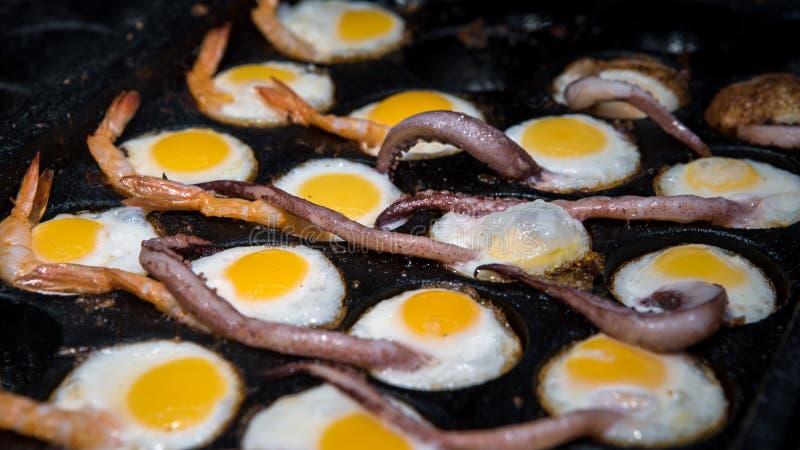 Un venditore ambulante prepara le uova di quaglia fritte con i tentacoli ed i gamberetti del calamaro fotografie stock