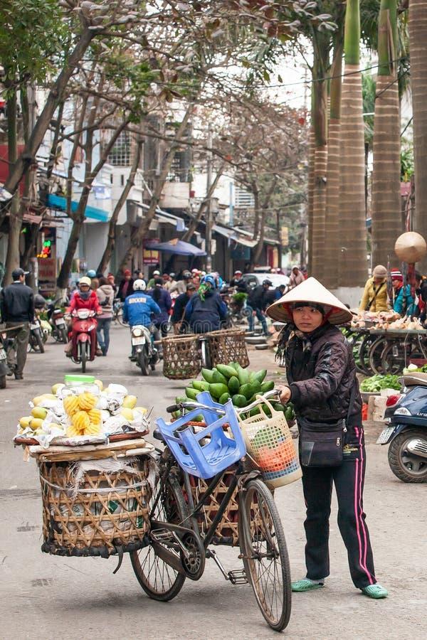 Un venditore ambulante vietnamita femminile con la vecchia bicicletta e frutti sui canestri di bamb? sulla via di Lao Kai, confin fotografia stock libera da diritti