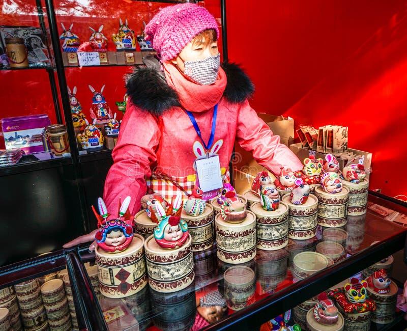 Un venditore femminile di cinese tradizionale handcraft della scultura di argilla, sulla fiera del tempio di festival di primaver fotografia stock libera da diritti