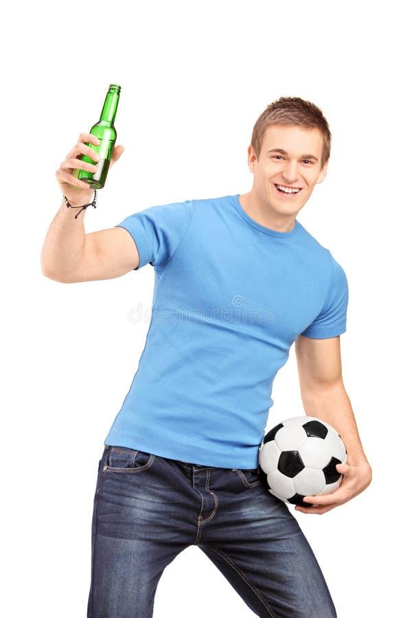 Un ventilador eufórico que lleva a cabo animar de la botella y del fútbol de cerveza fotos de archivo