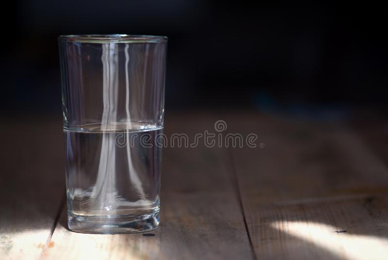 Un verre à moitié vide ou à moitié plein de l'eau photos stock