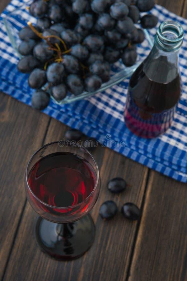 Un verre à vin de jeune vin rouge avec la bouteille en verre et un groupe de g photographie stock