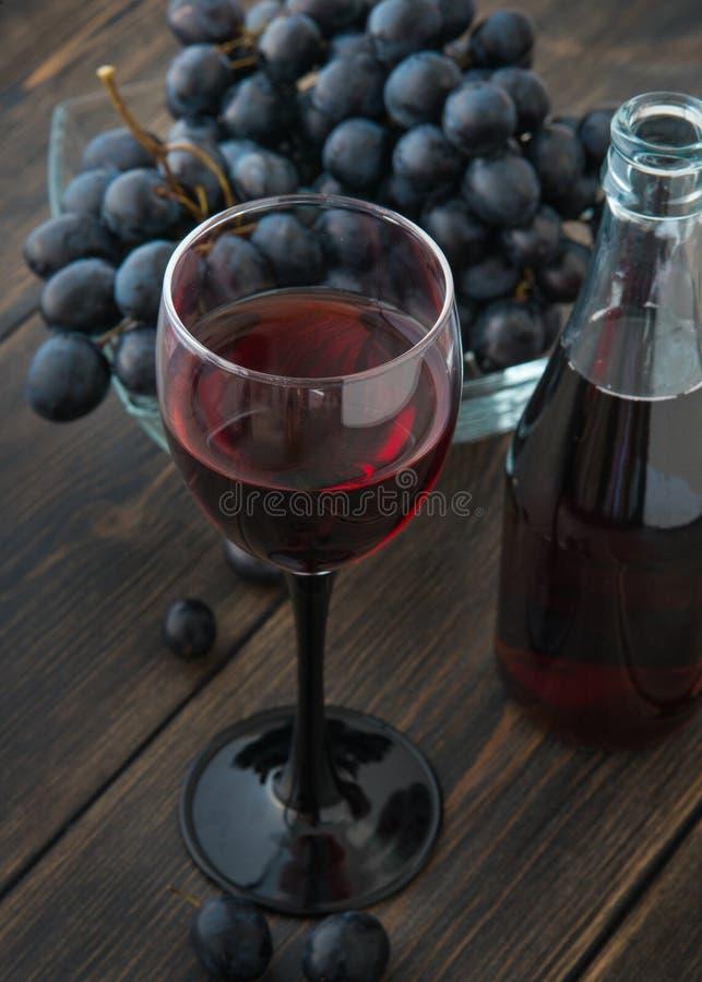 Un verre à vin de jeune vin rouge frais avec des bouteilles en verre et un petit pain photo stock