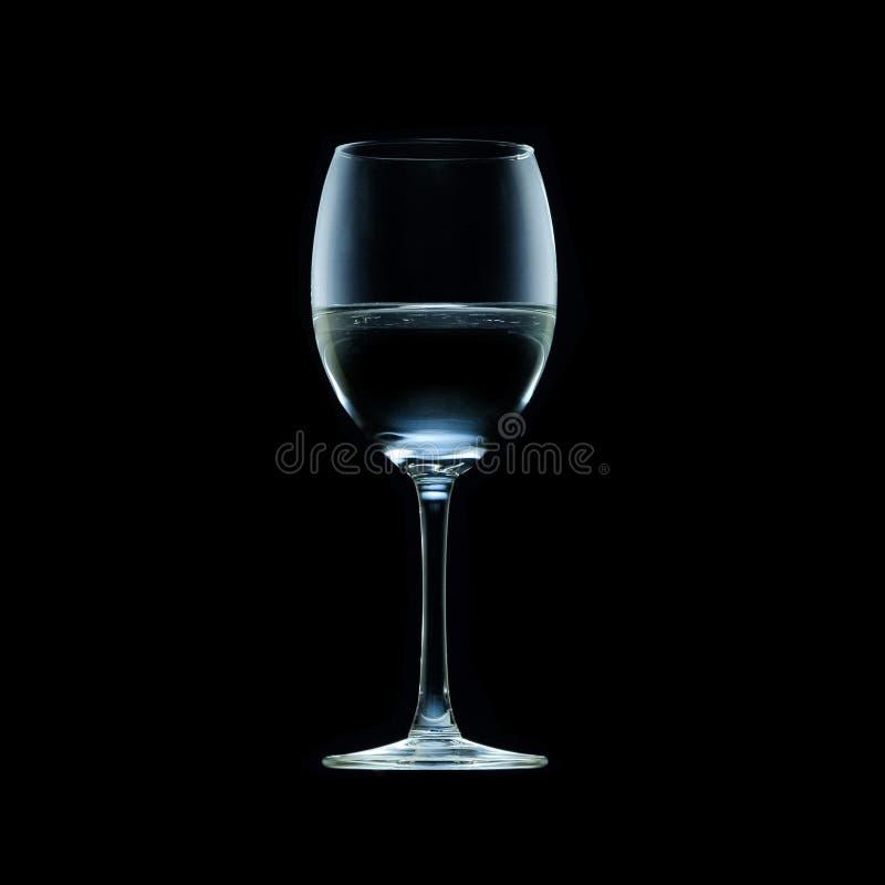 Un verre à vin à moitié plein de l'eau d'isolement sur le fond noir photo stock