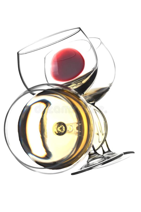 Un verre à vin rouge et un verre de vin blanc sur une surface de miroir avec des réflexions photos libres de droits