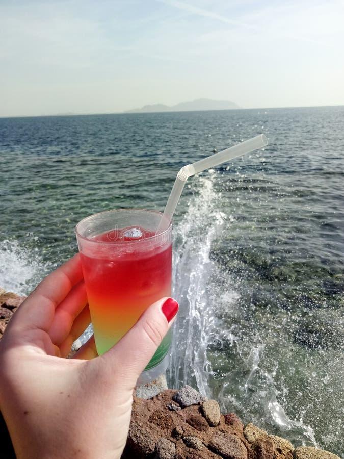 Un verre avec un cocktail coloré de souffle dans une main femelle contre le Th photo stock