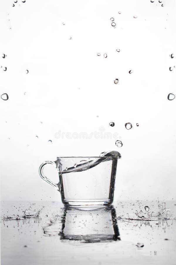 Un verre d'eau est sur la table humide fond blanc avec des baisses en baisse de l'eau Réflexion et petites baisses sur une surfac photo libre de droits
