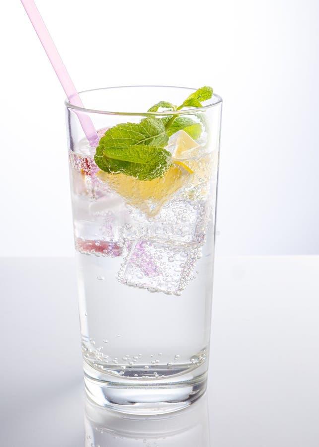 Un verre d'eau minérale décoré d'une tranche d'orange et de menthe photos stock