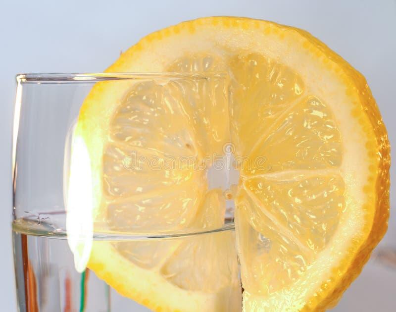 Un verre d'eau propre et une tranche de citron frais images libres de droits