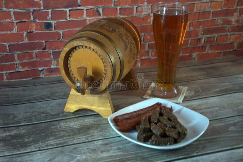 Un verre de bière blonde, d'un barillet et d'un plat avec des casse-croûte sur la toiture contre le mur de la brique rouge Plan r photo stock