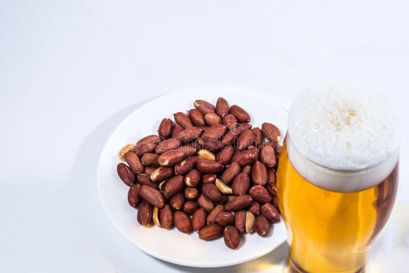 Un verre de bière et d'arachides dans la soucoupe image libre de droits