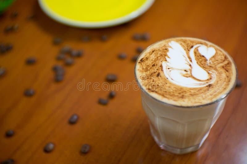 Un verre de café avec le dernier art de cygne et de grain de café sur le bois t photo libre de droits