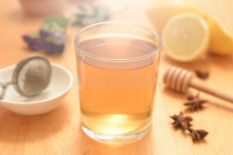Un verre de camomille avec quelques graines naturelles de miel et d'anis photographie stock
