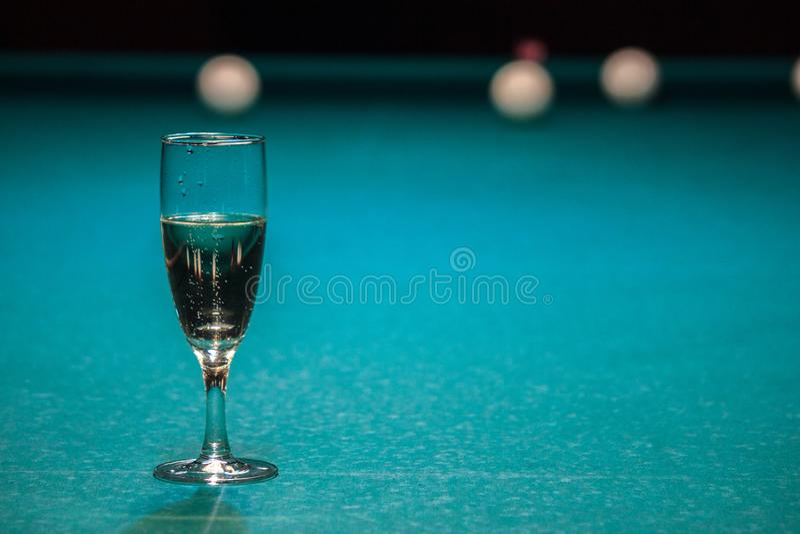 Un verre de champagne est sur la table de billard le gagnant du jeu, le champion boit un verre de vin mousseux Passe-temps, sport image libre de droits
