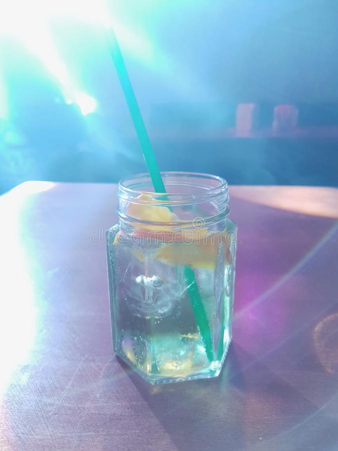 Un verre de cocktail avec la paille, le citron et les cubes de glace placés sur la table dans la barre de nuit, restaurant tandis images stock