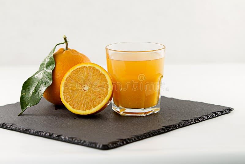 Un verre de invitation plein du jus d'orange, d'une demi orange et entière avec la feuille d'un plat carré d'ardoise sur le fond  photo stock