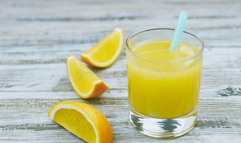 Un verre de jus d'orange frais avec les agrumes frais sur une table en bois l?g?re Vue horizontale Jus d'agrumes images stock