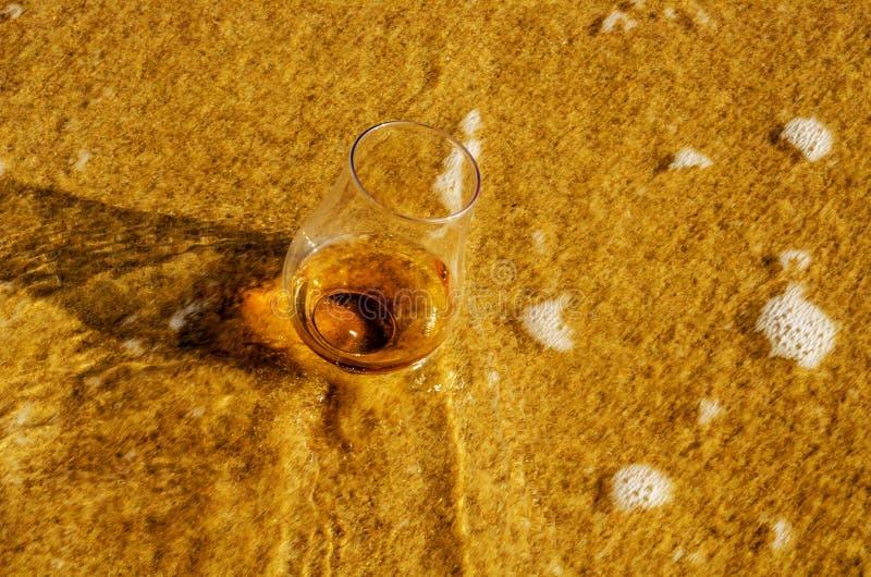 Un verre de malt simple de whiskey sur le sable a lavé par les vagues, images libres de droits