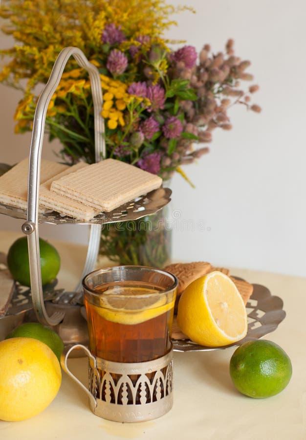 Un verre de thé noir en support en verre, quelques bonbons, citrons mûrs et chaux sur une surface de toile sur le fond léger photographie stock libre de droits