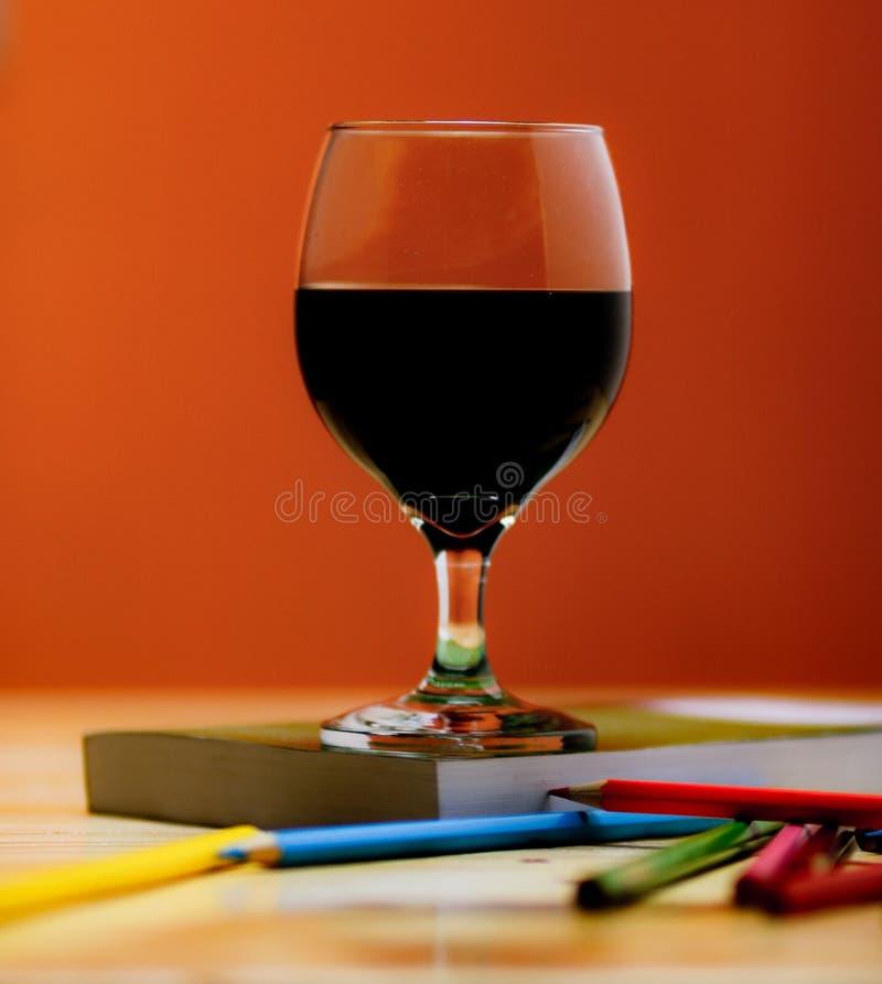 Un verre de vin accompagné d'une bonne lecture photo stock