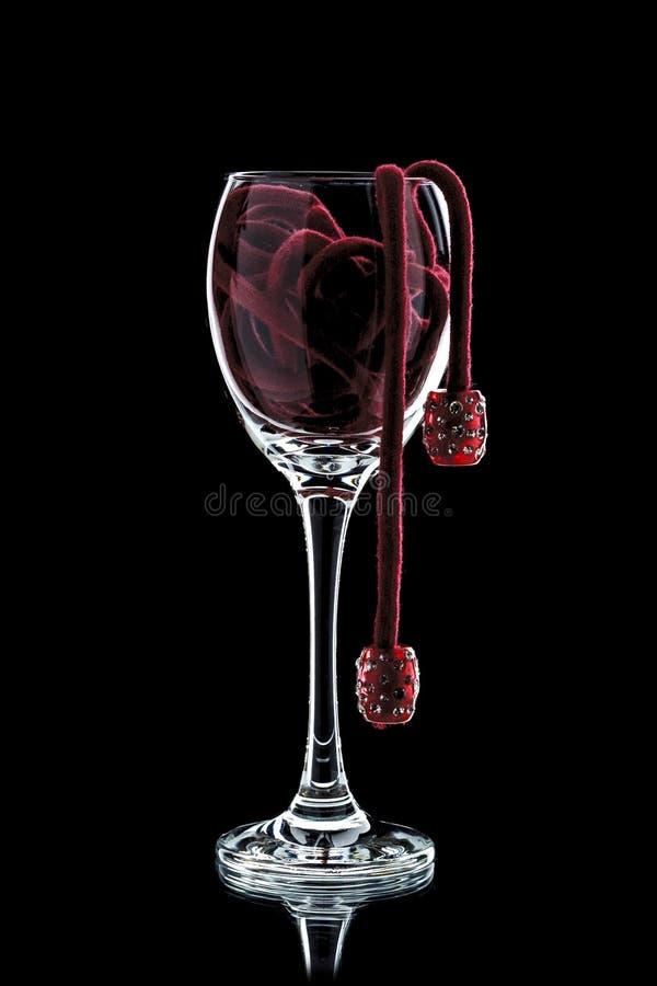 Un verre de vin avec le rouge perle la décoration à l'intérieur du plan rapproché sur a image libre de droits